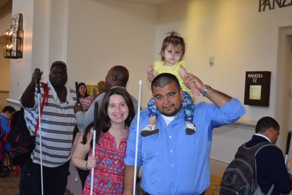 Blind parents pose at the NFB National Convention with their child sitting on the father's shoulders.