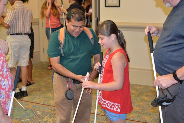 A blind man helps a blind girl use her long white cane.