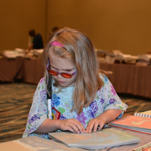 A young girl reads a Braille book at the 2018 National Convention.