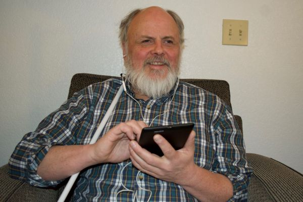 A man sits in a chair holding an iPad and listens to NFB-NEWSLINE with headphones.