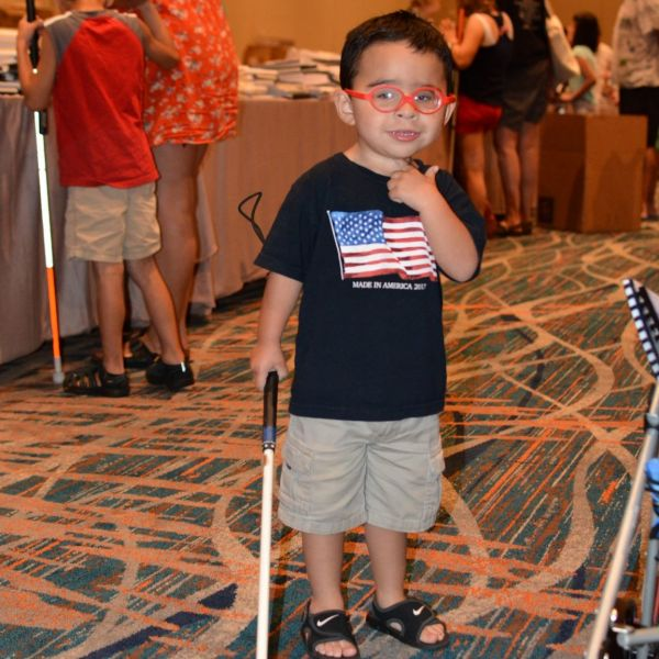 A young boy holds a white cane and gives the thumbs up sign.