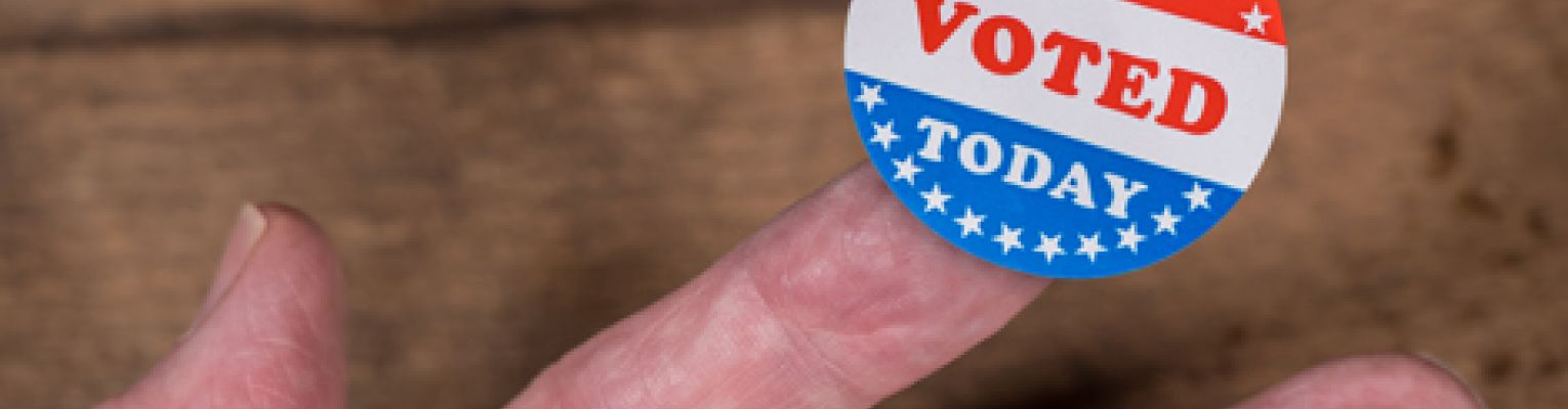 "An ""I voted"" sticker rests on a person's finger."