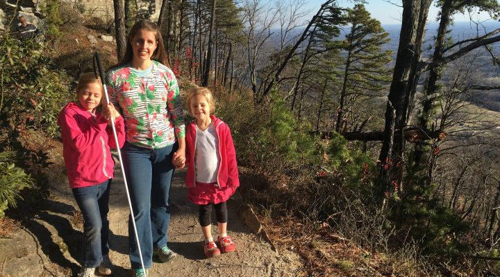 A blind family poses for a picture on a hiking trail.
