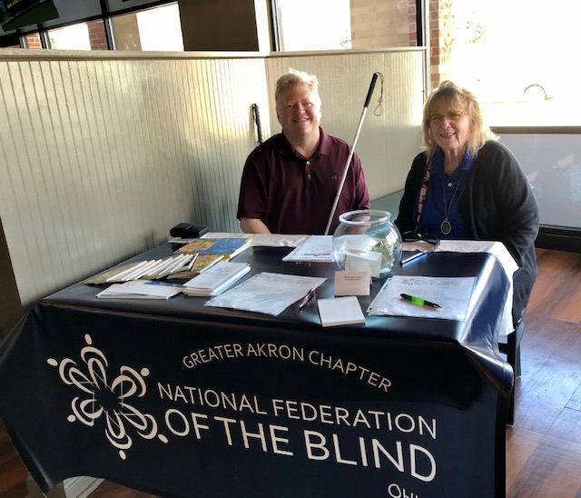 A man and a woman with white canes sit at a table with a banner on it that says Greater Akron Chapter, National Federation of the Blind.