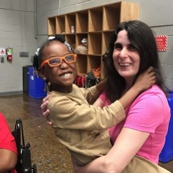 A woman holds a young girl with glasses in her arms; both are smiling.