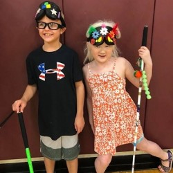 A young boy and a young girl both wear decorated sleep shades and stand holding their long white canes.