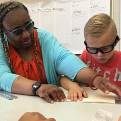 A woman and a young boy read Braille together.
