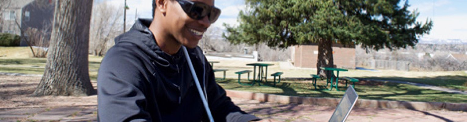 A young blind man sits at a picnic table in the park using a laptop.