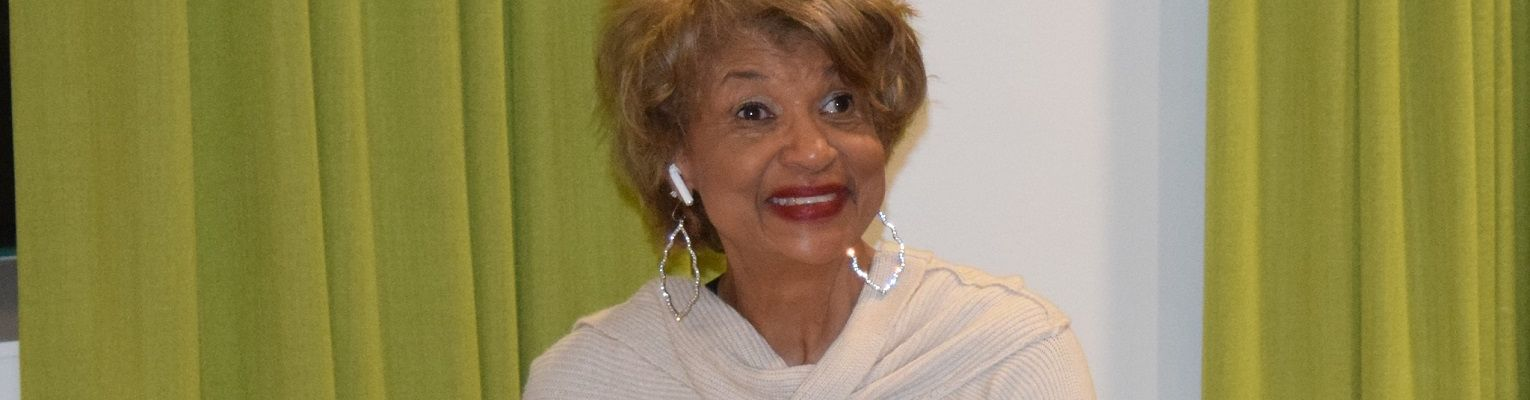 Ever Lee Hairston smiles as she sits by a piano during an NFB National Convention.