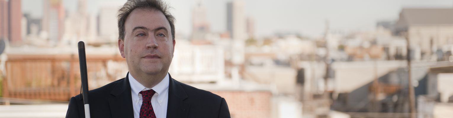 President Riccobono stands outside with view of Baltimore behind him