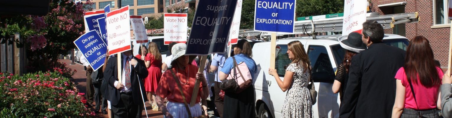"A protest with blind protesters holding signs that say ""Vote No on Subminimum Wages"" and ""Do You Support Equality or Exploitation?"""