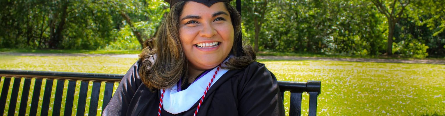 A smiling Kenia Flores in her graduation cap and gown sits on a bench outside.