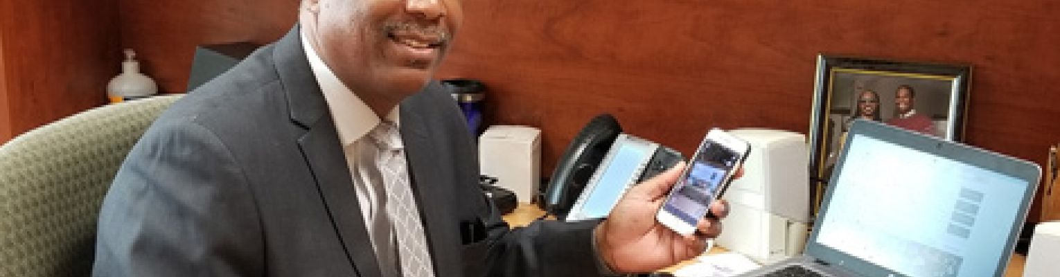 Anil Lewis smiling at his desk holding his iPhone.