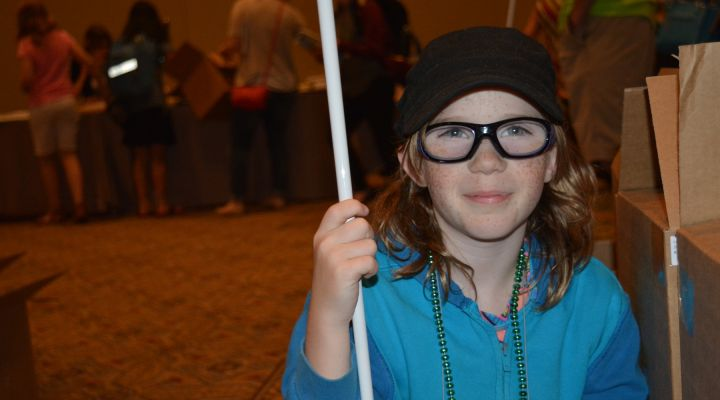 A young girl with a white cane and glasses.