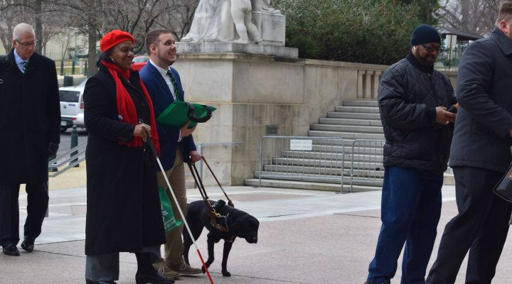 Black, blind woman with white cane and white blind man with guide dog wait in line outside representative building during previous Washington Seminar