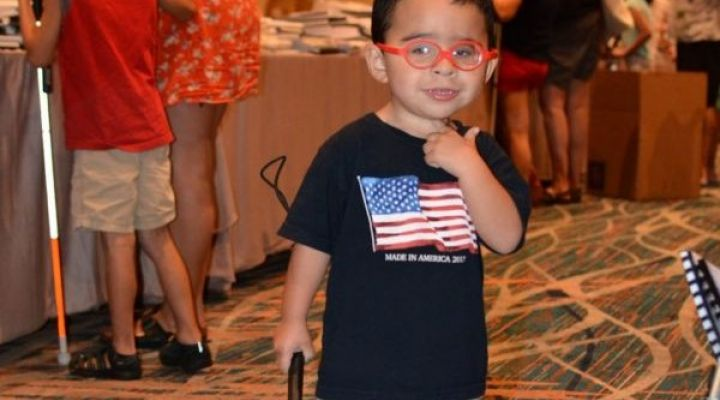 A boy with a white cane gives the thumbs up during the national convention.