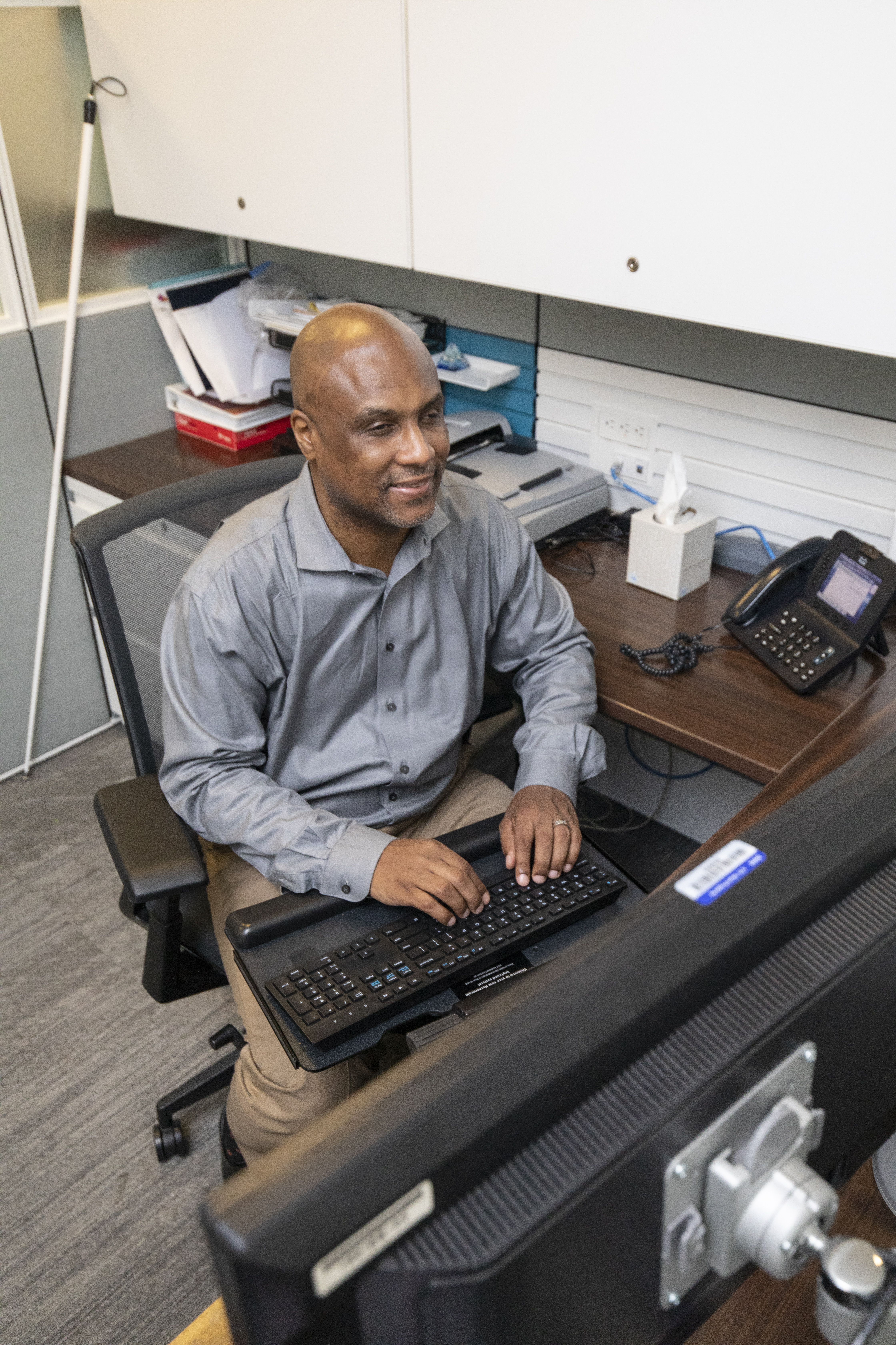 A man works at his computer in a cubicle with a long white cane leaning in the corner behind him.