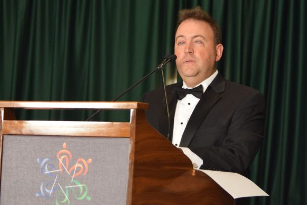 NFB President Mark A. Riccobono stands at a podium in a tuxedo as he delivers his banquet speech.