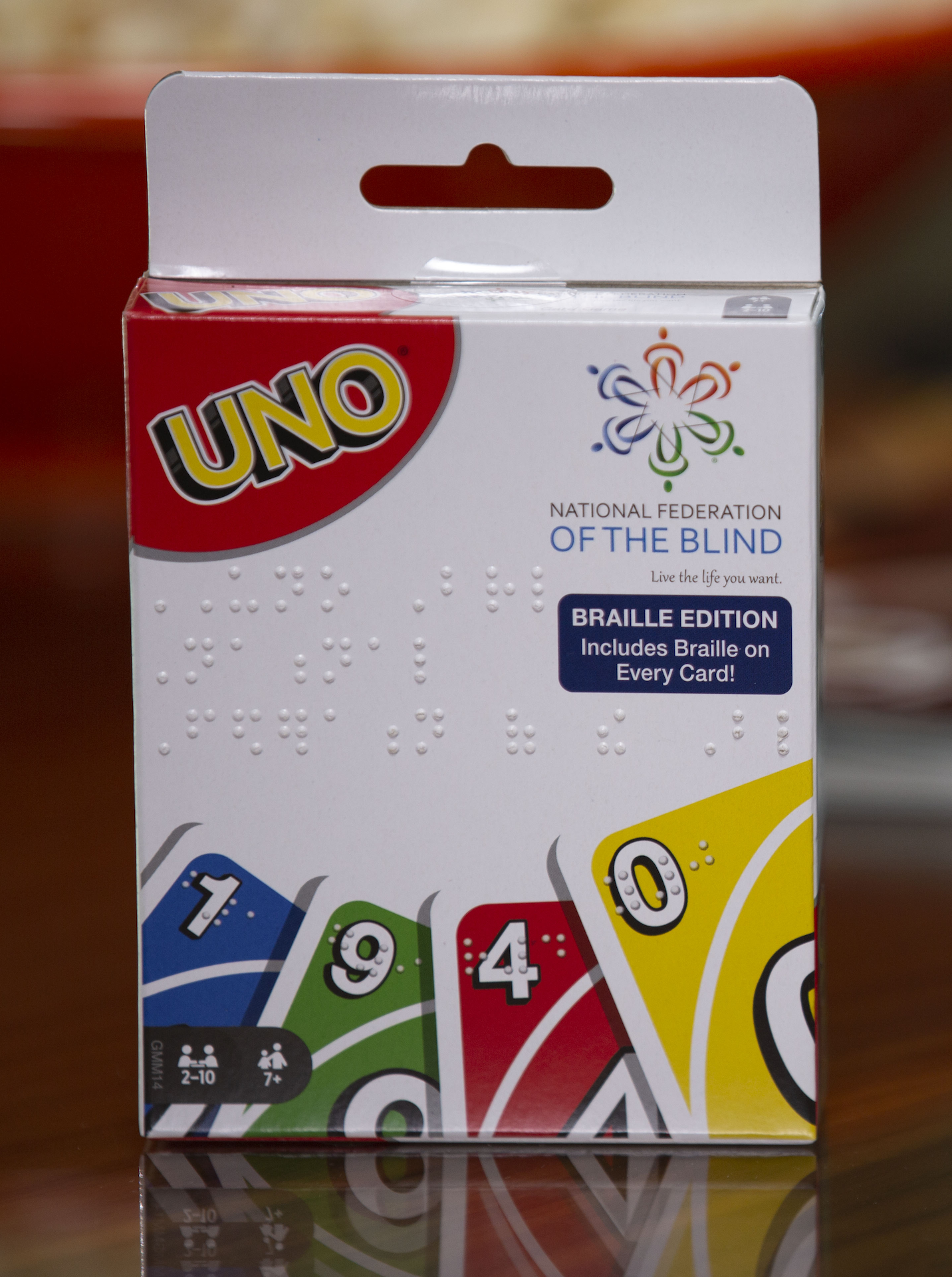 Front of new UNO Braille packaging that displays tactile Braille and the NFB logo.