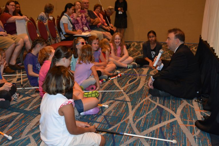 NFB President Mark A. Riccobono sits on the floor and talks with blind children.