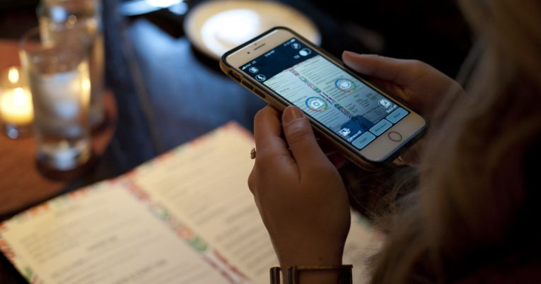 A woman holds a smart phone with KNFB Reader over a menu in a restaurant.