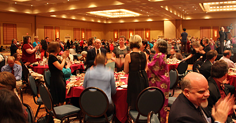 Convention goers clapping and giving a standing ovation after a banquet speech.