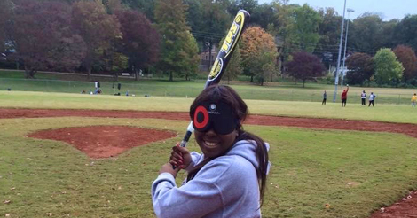 LaKeisha Holmes stands on a field wearing a blindfold and holding a baseball bat.