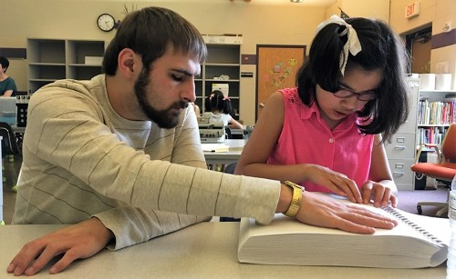 A blind adult examines a Braille book with a young student.