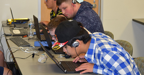 Four blind students work on laptop computers while wearing headphones.