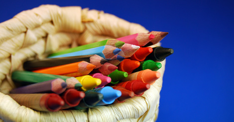Lots of colorful crayons in a basket with a blue background.