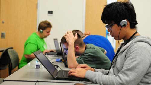 Students at NFB Youth Slam work on laptops.