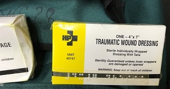A box of wound dressing labeled with Braille sits on top of a large backpack of supplies.
