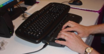 A person's hands rest on a Braille display in front of a computer.