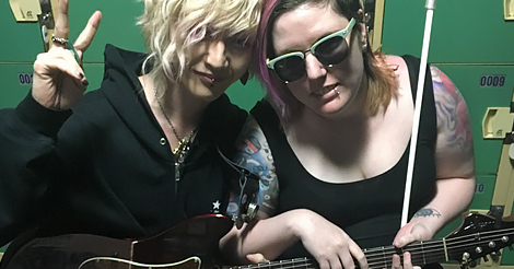 In Japan, Caitlin and a friend sit holding a guitar and a white cane.
