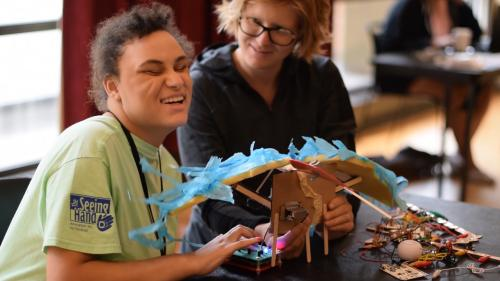 Camryn smiles while working on a motorized bird as part of the installation art project.