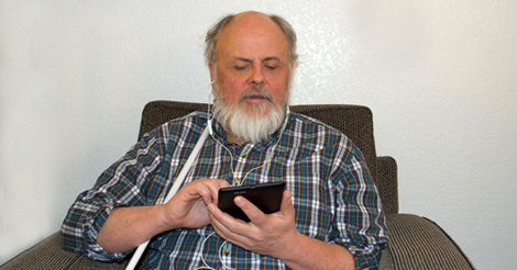 A man with a beard holds a tablet device while sitting in an armchair with a white cane resting on his right shoulder.