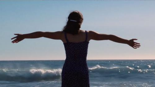 Sarah stands on the beach with her arms outstretched.