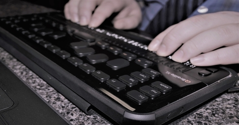 A person's hands rest on a HIMS QBraille XL device.