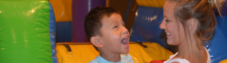 Four-year-old boy smiles in the bounce house with his sister at the 2018 National Convention.