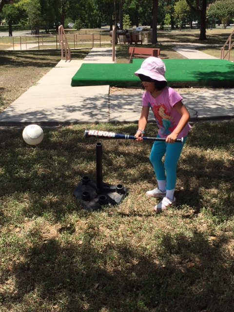 EmmaGrace smacks a ball off the tee while wearing learning shades (San Antonio, TX).