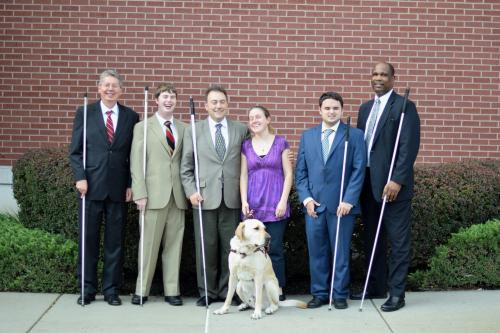 John Pare, Michael Ausbun, Mark Riccobono, Julie McGinnity, Jerad Nylin, and Anil Lewis pose in front of the NFB Jernigan Institute.