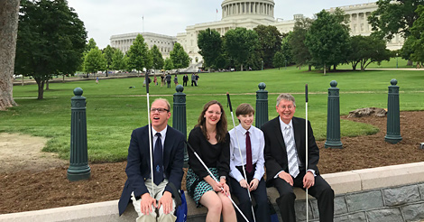 Interns Matt Langland, Grace Anderson, and Ellana Crew sit on a stone wall alongside John Paré in front of the U.S. Capitol in Washington, DC.