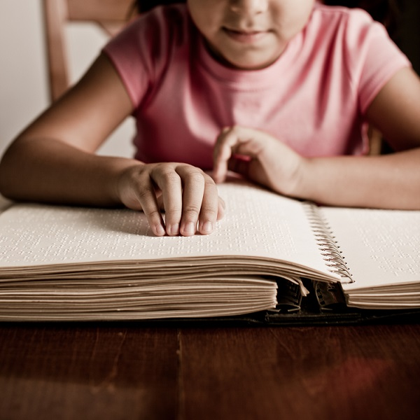 A young girl reads Braille paper.