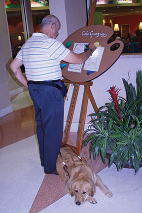 Senior with a guide dog using a device to read