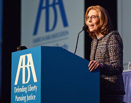 American Bar Association president, Linda Klein, stands behind a podium and speaks into a microphone.