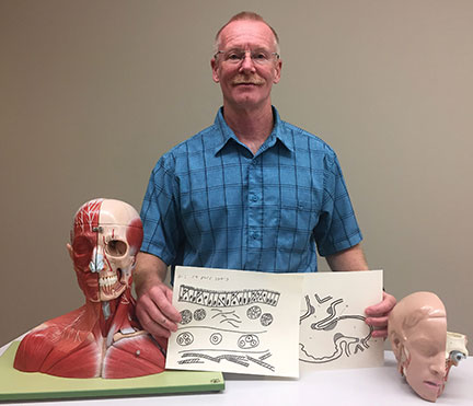 Dr. Paul Barlett displays models of the human body, and tactile drawings that he used to teach a blind student in the chiropractic field.