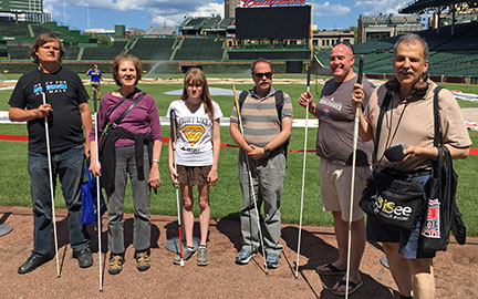 Six participants in the NFB of Illinois's FreedomLink program stand on the field at Wrigley Field in Chicago.