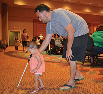 A dad helps his toddler daughter learn to use her long white cane.