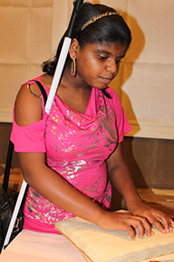 A young blind girl reads Braille