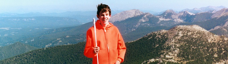 A boy with a white cane stands at the peak of a mountain.